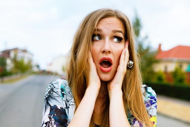 クレイジーヒップスターブロンドの女性の面白い屋外のポートレート、彼女の頬に手を入れて、驚きの感情。
