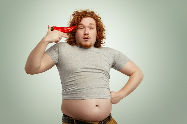 Funny overweight fat man with curly ginger hair holding big chile pepper at his temple like pistol