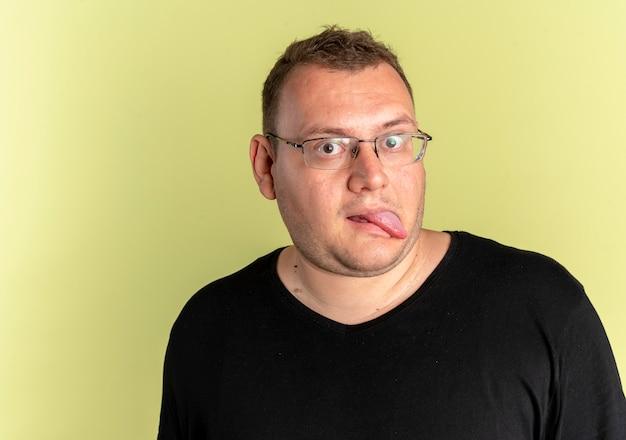 Uomo divertente in sovrappeso con gli occhiali che indossa la maglietta nera che attacca fuori la lingua sopra la luce