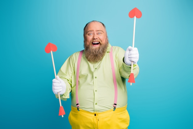 Funny overweight man hold heart shape arrows on blue background