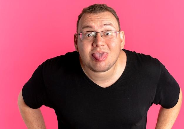 ピンクの壁の上に立っている舌を突き出ている黒いtシャツを着ている眼鏡の面白い太りすぎの男
