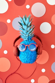 Funny painted pineapple in sunglasses and earphones on red paper with circles