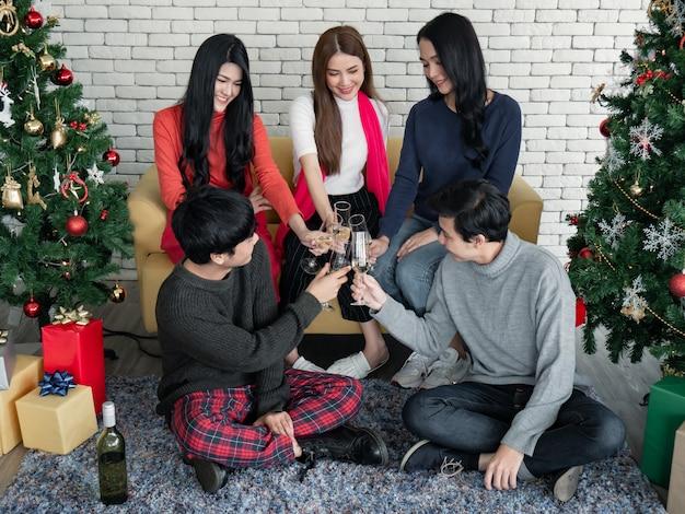 クリスマスフェスティバルを祝うために、チャリンという音を立ててグラスを飲み、家でワインを飲んだ若いアジア人の面白いパーティー。家で新年を祝う。ギャングティーンタイのメリークリスマスと幸せな休日。