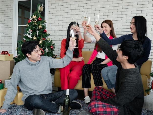 クリスマスフェスティバルを祝うために、チャリンという音を立ててグラスを飲み、家でワインを飲んだ若いアジア人の面白いパーティー。家で新年のお祝い。ギャングティーンタイのメリークリスマスと幸せな休日。