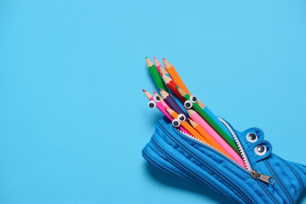 Funny pencil case eating pencils on blue