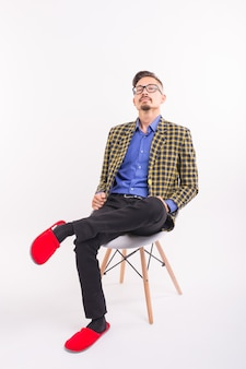 Funny people concept - man sitting on chair in red slippers. he is in checked suit and glasses.