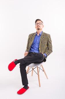Концепция забавных людей - человек, сидящий на стуле в красных тапочках. он в клетчатом костюме и очках.