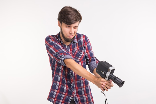 Funny people, photo and vintage concept - young man using vintage camera on white surface