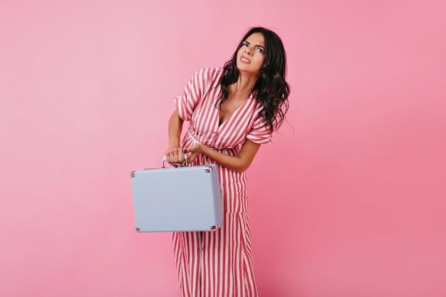 Foto divertente della signora riccia in prendisole rosa. la ragazza solleva appena la valigia blu pesante.