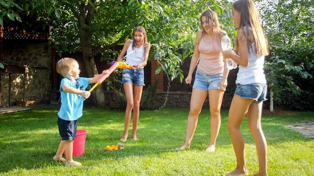 Смешное фото счастливой семьи с детьми, играющими и плещущими воду из водяных пистолетов и садового шланга в жаркий солнечный день
