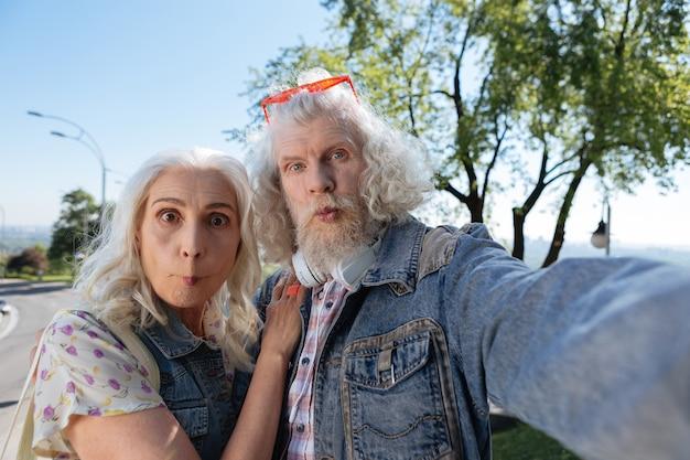 Прикольная фотка. позитивные пожилые люди гримасничают, делая смешное фото