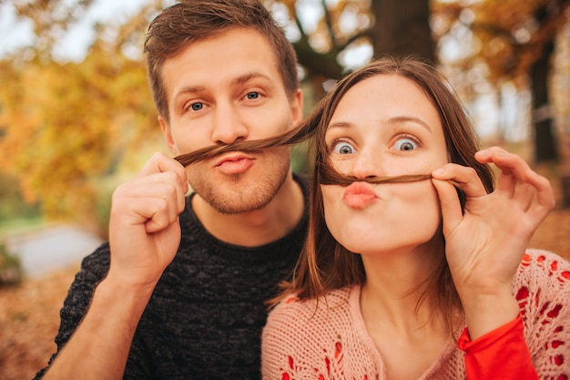 Funny picture of couple playing on camera. they hold pieces on hair like moustache. couple is in autumn park.
