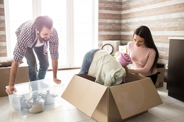 Funny picture of girl that is trying to find something in the box. her parent are working besides her and laughing from the situation. father is holding box of pans while the woman is holding a towel.