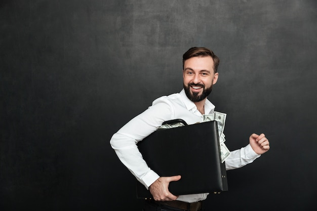 Funny picture of lucky man holding black briefcase full of dollar banknotes inside, isolated over dark gray