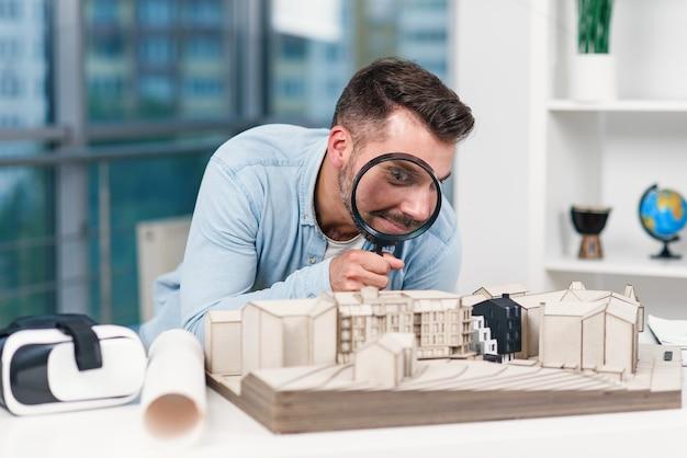 남성 건축가의 재미있는 그림은 돋보기를 통해 집 모델을 찾습니다. 주택 검사 및 부동산 개념.