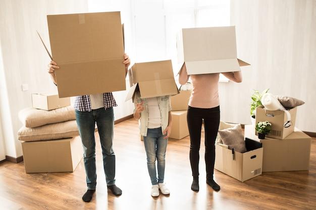 Смешная картина трех человек, которые надели коробки на головы. они играют в какую-то игру. этим людям очень весело.