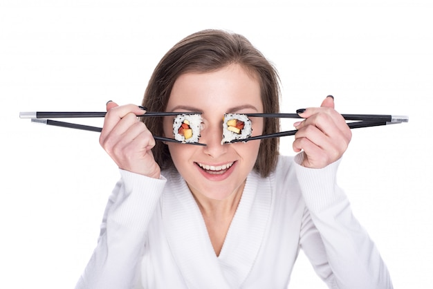 Funny picture of woman is holding sushi rolls on her eye.