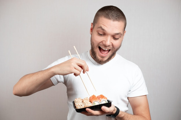 Funny picture of young man is holding sushi rolls on white background