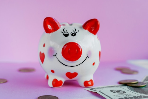 Funny piggy bank and on pink background