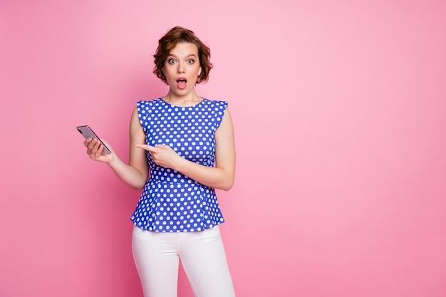 Забавная девушка в стиле пин-ап держит телефон прямо пальцем