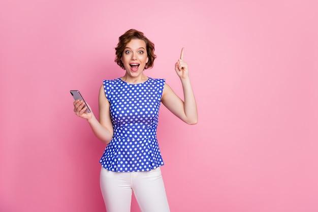 Забавная девушка в стиле пин-ап держит телефон взволнованная идея