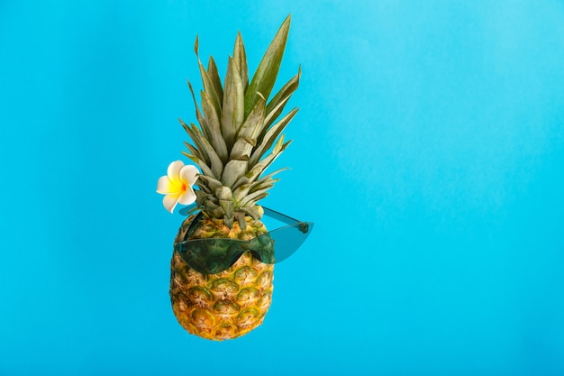 Funny pineapple male face in green sunglasses plumeria flower. tropical summer fruits levitating creative summer pineapple on color blue summer background.