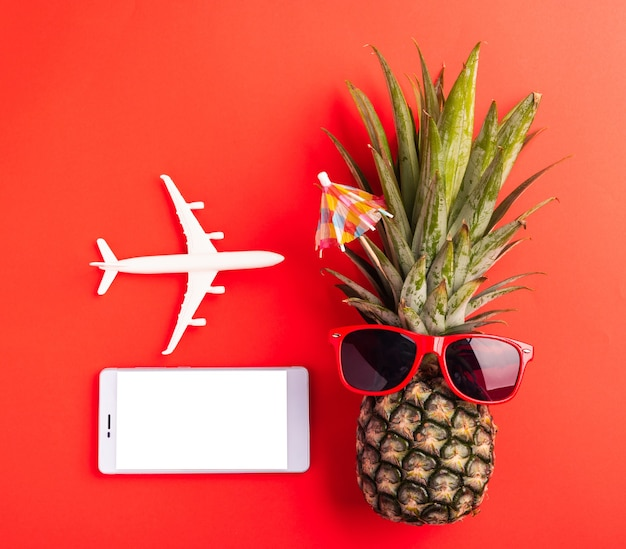 Funny pineapple wear red sunglasses, model plane, and smartphone blank screen, flat lay