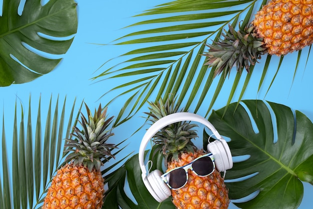 Funny pineapple wearing white headphone, concept of listening music, isolated on blue background with tropical palm leaves