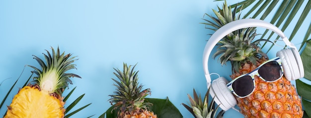 白いヘッドフォンを身に着けている面白いパイナップル、音楽を聴くという概念、熱帯のヤシの葉、上面図、フラットレイデザインで色付きの背景に分離されました。
