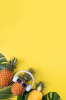白いヘッドフォンを身に着けている面白いパイナップル、音楽を聴く、熱帯のヤシの葉で黄色の背景に分離、上面図、フラットレイデザインコンセプト。