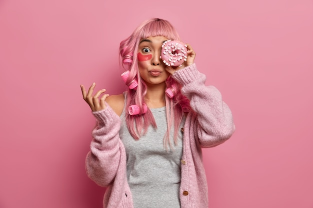 Funny pink haired asian woman has rollers on head, covers eye with tasty sweet doughnut, wears collagen patches to reduce wrinkles