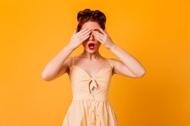 손으로 눈을 덮고 재미있는 핀 업 소녀. 노란 공간에 고립 된 드레스에 놀라운 생강 여자의 스튜디오 샷.