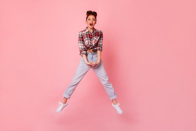 ジャンプしてカメラを見ているブルージーンズの面白いピンナップガール。ピンクの空間で踊る市松模様のシャツを着た若い女性の全身像。