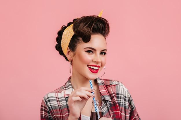 ピンクの背景に笑っている面白いピンナップガール。ひび割れたシャツを着たトレンディなブルネットの女性のスタジオショット。