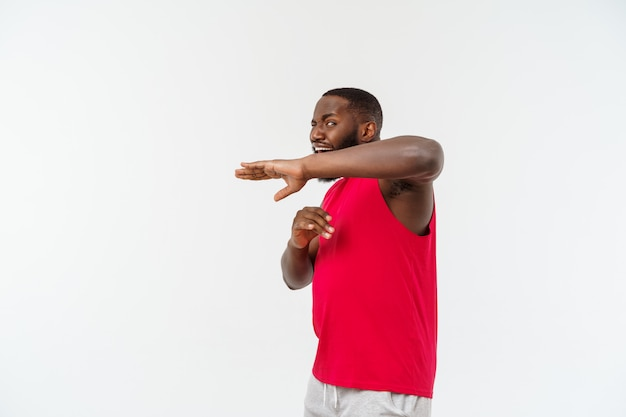 Funny and playful adult african american guy standing in profile in martial arts pose with raised palms, frowning and staring.