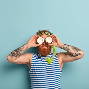 Divertente e giocoso uomo barbuto indossa maschera da snorkeling, si prepara per le immersioni subacquee, tiene due noci di cocco sugli occhi