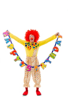 Funny playful clown in red wig holding