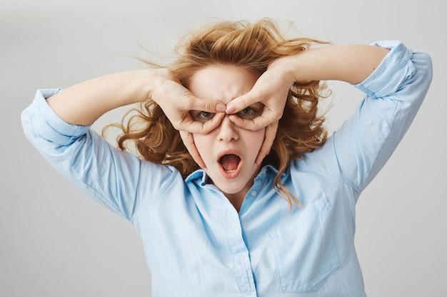 Забавная игривая кудрявая девушка делает маску на руки, имитируя супергероя