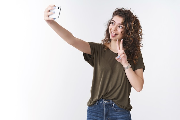 Funny playful cute georgian young curly-haired girlfriend taking selfie send boyfriend via internet app extend arm upwards holding smartphone show tongue victory or peace gesture, white background
