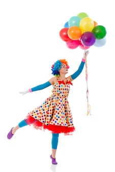 Funny playful female clown in colorful wig holding balloons.