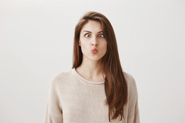 Divertente ragazza giocosa strabismo e facce imbarazzanti