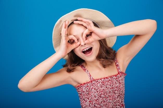 Смешная игривая маленькая девочка в шляпе делает очки руками на синем фоне
