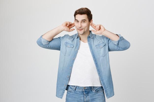 Uomo giocoso divertente che mostra le orecchie e le smorfie