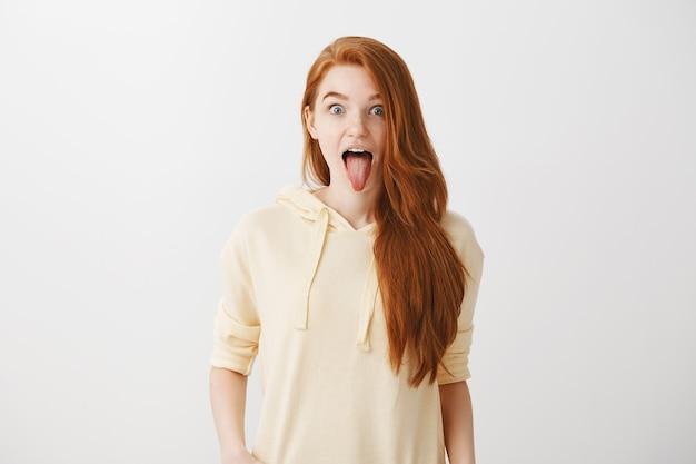 舌を見せて興奮している面白い遊び心のある赤毛の女の子