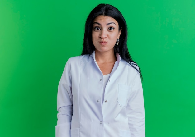 Divertente giocoso giovane dottoressa che indossa guance sbuffanti abito medico isolato sulla parete verde con lo spazio della copia