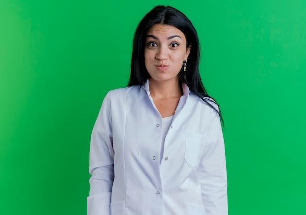 복사 공간 녹색 벽에 고립 된 의료 가운 피 뺨을 입고 재미 장난 젊은 여성 의사