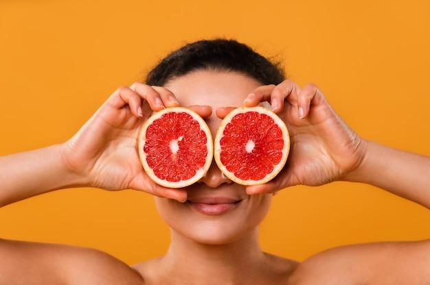 彼女の目に柑橘系の果物の半分を保持している市松模様のシャツの面白い遊び心のある若い女性