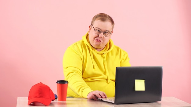 Funny plump man in a yellow hoodie grimaces while sitting at a laptop. a person has fun as much as possible sitting at home