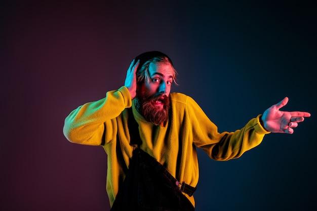 Divertente che indica a lato. ritratto dell'uomo caucasico sul fondo dello studio sfumato in luce al neon. bellissimo modello maschile con stile hipster. concetto di emozioni umane, espressione facciale, vendite, annuncio.