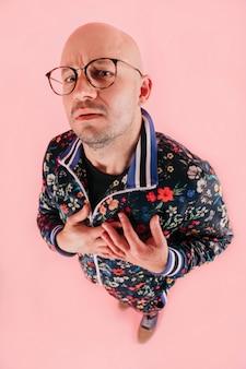 メガネのスタイリッシュな男の上から面白い肖像画は、表情で心に彼の手を保持します